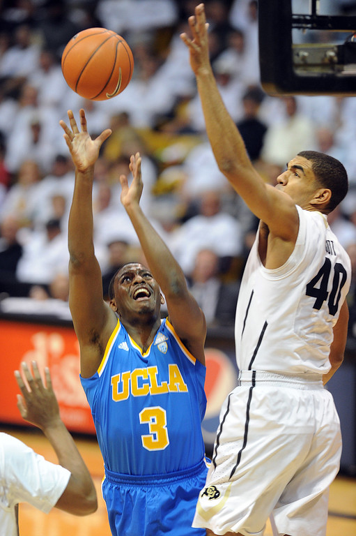 . Josh Scott of CU blocks the shot of Jordan Adams of UCLA during the first half of the January 16, 2014 game in Boulder.  (Cliff Grassmick/Daily Camera)