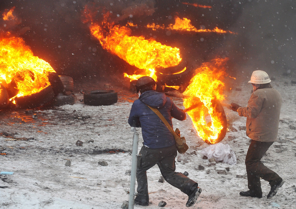 . Protestors place burning tires as they clash with police in the center of Kiev on January 22, 2014. At least two activists were shot dead today as Ukrainian police stormed protesters\' barricades in Kiev, the first fatalities in two months of anti-government protests. Pitched battles raged in the centre of the Ukrainian capital as protesters hurled stones at police and the security forces responded with tear gas and rubber bullets. AFP PHOTO / GENYA SAVILOV/AFP/Getty Images