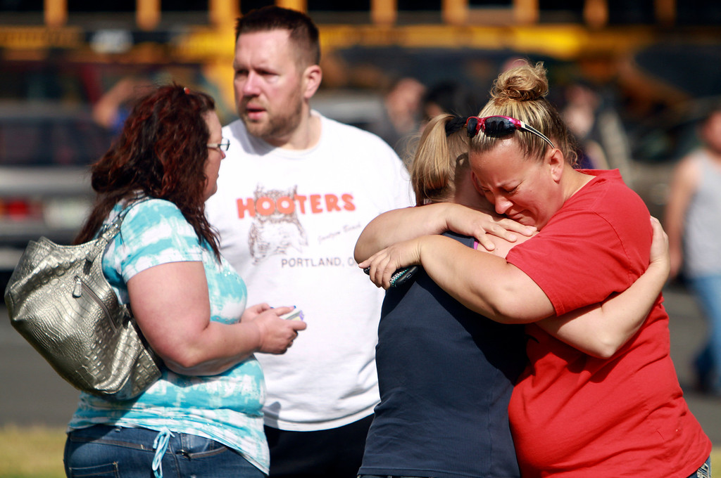 . People comfort eachother as they await hear about the safety of students after a shooting at Reynolds High School Tuesday, June 10, 2014, in Troutdale, Ore. A gunman killed a student at the high school east of Portland Tuesday and the shooter is also dead, police said. (AP Photo/The Oregonian, Faith Cathcart)