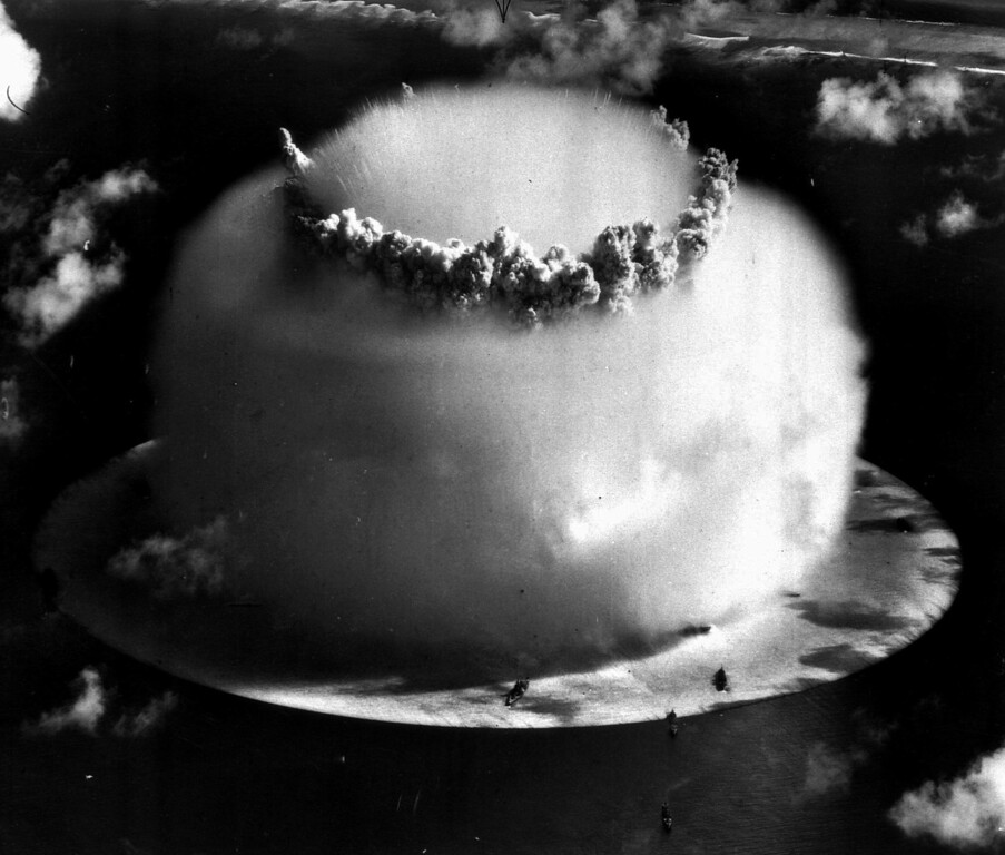 ". A huge mushroom cloud rises above Bikini atoll in the Marshall Islands July 25, 1946 following an atomic test blast, part of the U.S. military\'s ""Operation Crossroads.\"" The dark spots in foreground are ships that were placed near the blast site to test what an atom bomb would do to a fleet of warships. (AP Photo/file)"