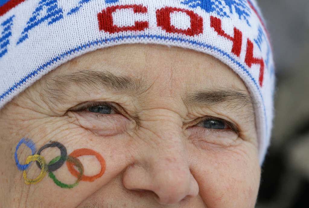 . An elderly woman has the Olympic rings painted on her cheek as she watches the men\'s biathlon 4x7.5K relay at the 2014 Winter Olympics, Saturday, Feb. 22, 2014, in Krasnaya Polyana, Russia. (AP Photo/Kirsty Wigglesworth)