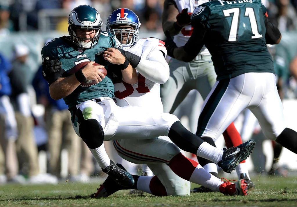 . New York Giants defensive tackle Linval Joseph (97) sacks Philadelphia Eagles\' Matt Barkley (2) during the second half of an NFL football game Sunday, Oct. 27, 2013, in Philadelphia. (AP Photo/Michael Perez)