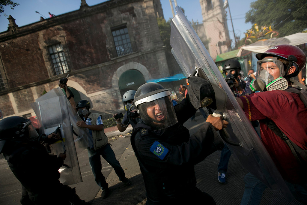 . A police officer yells at photographers to stop taking pictures of clashes with demonstrators who are marking the anniversary of the Tlatelolco massacre in Mexico City, Wednesday, Oct. 2, 2013. Mexico commemorated the 45th anniversary of the massacre of students holding an anti-government protest, killed by men with guns and soldiers in 1968, days before the Summer Olympics celebrations in Mexico City. (AP Photo/Eduardo Verdugo)