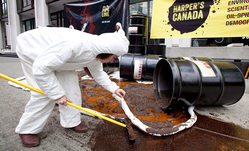 . A member of Greenpeace pretends to clean up a mock oil spill outside the Enbridge Northern Gateway pipeline office in downtown Vancouver, June 13, 2012.   (AP Photo/The Canadian Press, Jonathan Hayward)