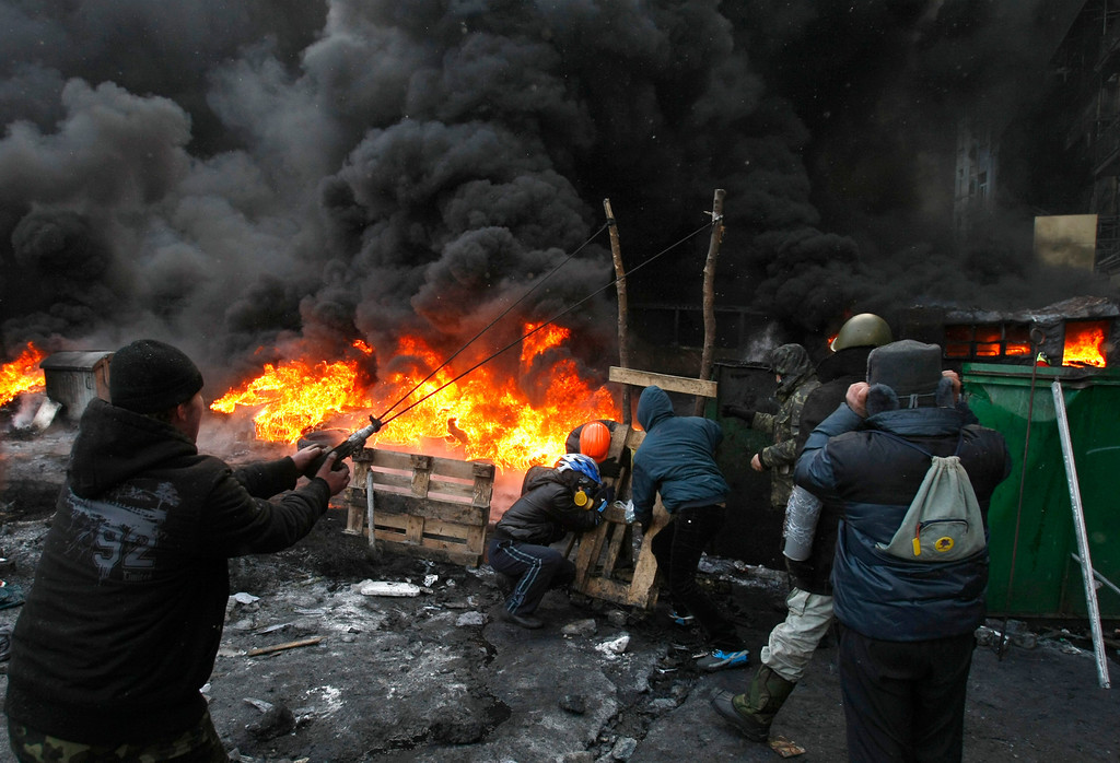 . Protesters use a large slingshot to hurl rocks at police in central Kiev, Ukraine, Thursday, Jan. 23, 2014. Thick black smoke from burning tires engulfed the downtown Ukrainian capital as an ultimatum issued by the opposition to the president to call early election or face street rage was set to expire with no sign of a compromise. (AP Photo/Darko Vojinovic)