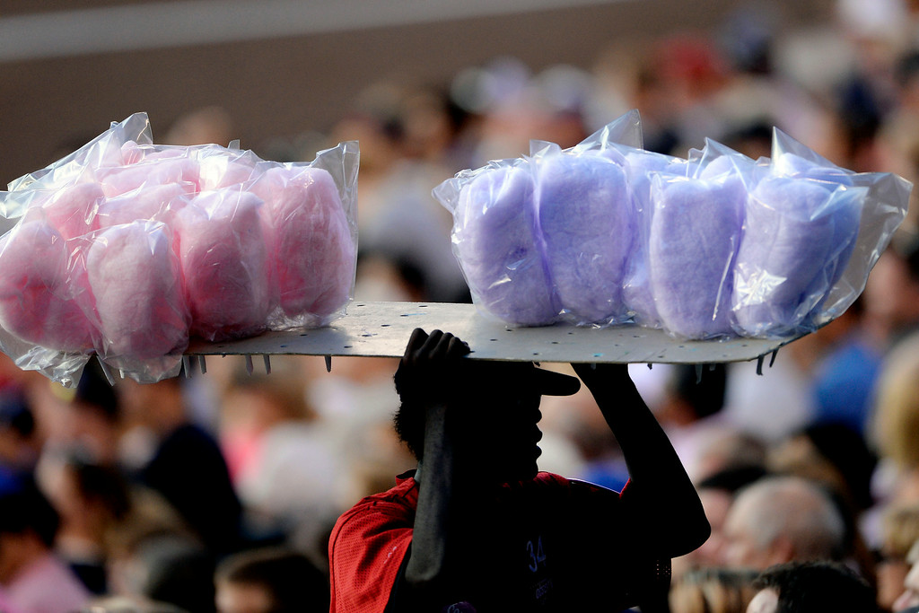 . A cotton candy vendor uses his head during the second inning between the Washington Nationals and the Colorado Rockies at Coors Field. Major League Baseball action between the Colorado Rockies and the Washington Nationals on Monday, July 21, 2014. (Photo by AAron Ontiveroz/The Denver Post)