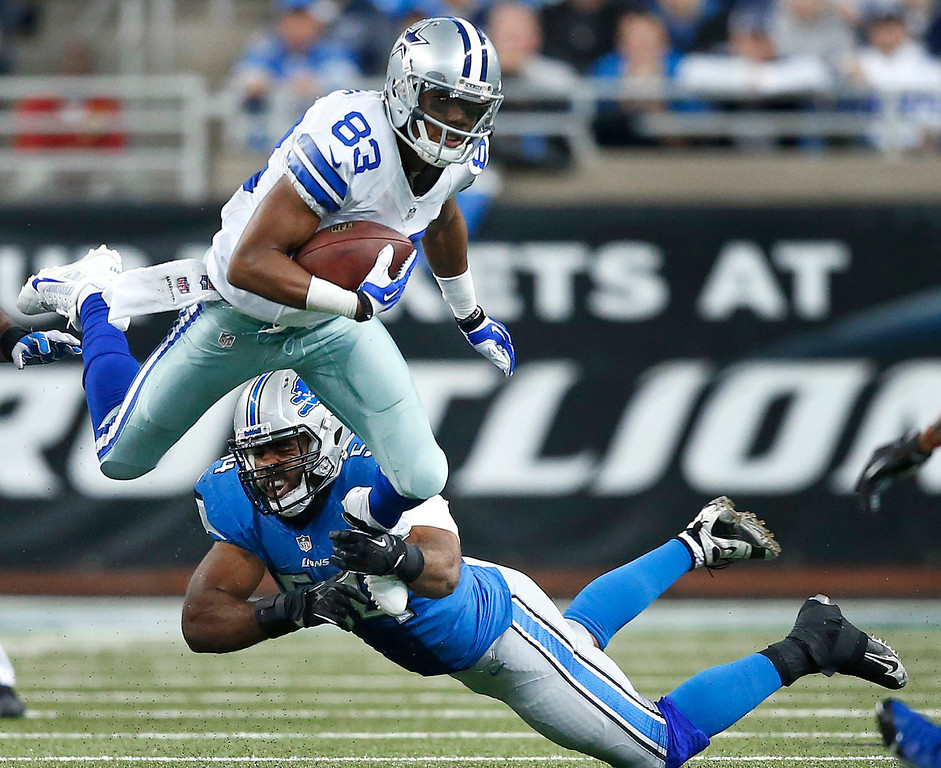 . Dallas Cowboys wide receiver Terrance Williams (83) jumps to elude Detroit Lions outside linebacker DeAndre Levy (54) in the second half of an NFL football game in Detroit, Sunday, Oct. 27, 2013. (AP Photo/Rick Osentoski)