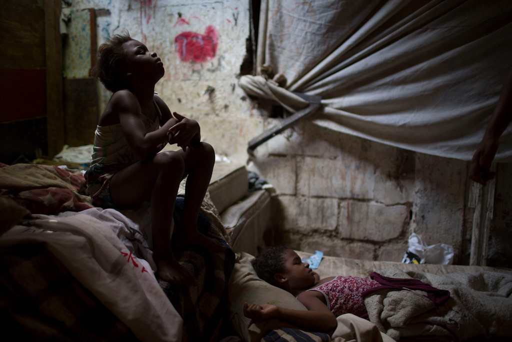 . Two sisters watch television inside their home in a poor area of the Mare slum complex in Rio de Janeiro, Brazil, Saturday, April 5, 2014. More than 2,000 Brazilian soldiers stormed into the Rio de Janeiro slum complex Saturday with armored personnel carriers and helicopters in a bid to improve security two months before the start of the World Cup. (AP Photo/Felipe Dana)