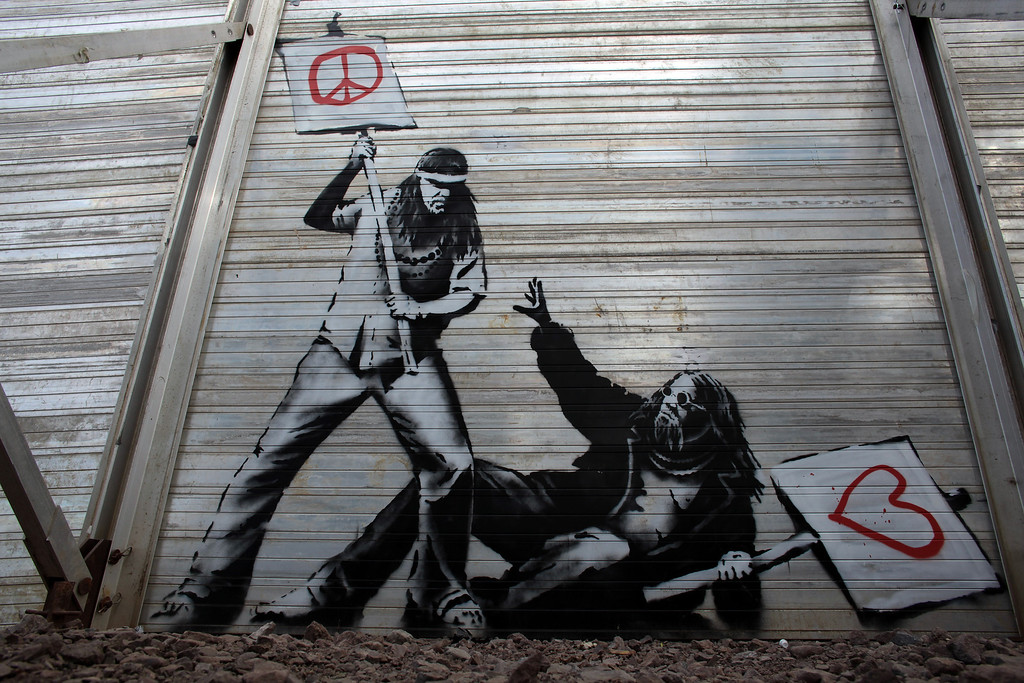 . Art work said to be by underground artist Banksy is seen on the fence at the Glastonbury Festival site at Worthy Farm, Pilton on June 24, 2010 in Glastonbury, England. The gates opened yesterday to what has become Europe\'s largest music festival and is celebrating its 40th anniversary. (Photo by Matt Cardy/Getty Images)