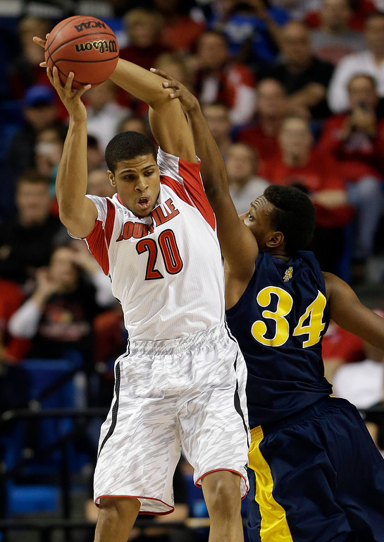 . Louisville guard/forward Wayne Blackshear (20) pulls down a rebound in front of North Carolina A&T forward Bruce Beckford (34) during the first half  their second-round NCAA college basketball tournament game on Thursday, March 21, 2013, in Lexington, Ky. (AP Photo/John Bazemore)