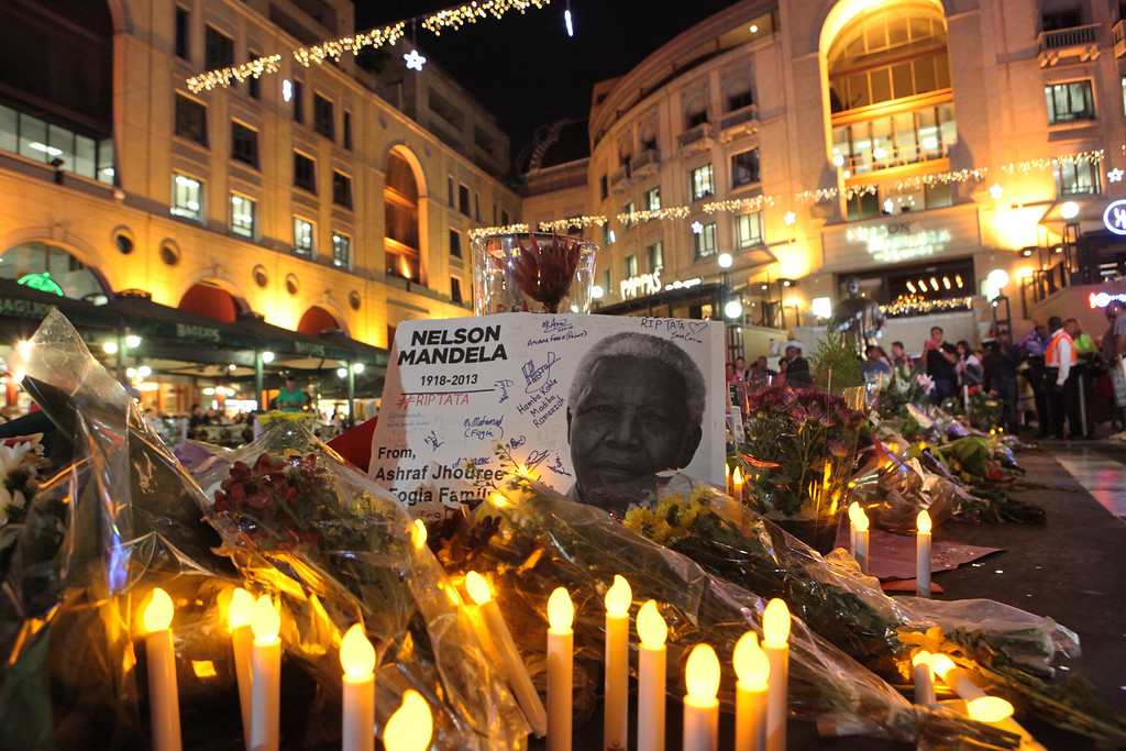 . Flowers, candles and condolence messages are seen in Nelson Mandela Square in Sandton, Johannesburg, South Africa, Saturday, Dec. 7, 2013. Mandela died Thursday at his Johannesburg home after a long illness. He was 95(AP Photo/Tsvangirayi Mukwazhi)