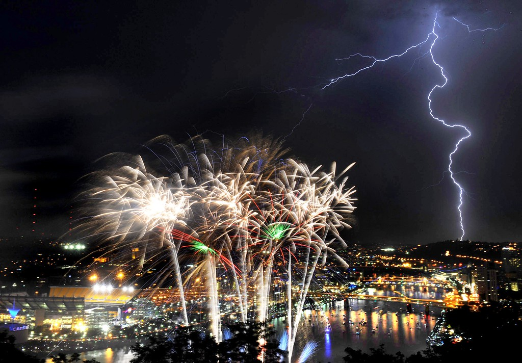 . Lightning flashes during Independence Day fireworks as viewed atop Mt. Washington on Grandview Ave. in Pittsburgh, Thursday, July 4, 2013. (AP Photo/Pittsburgh Post-Gazette, John Heller)