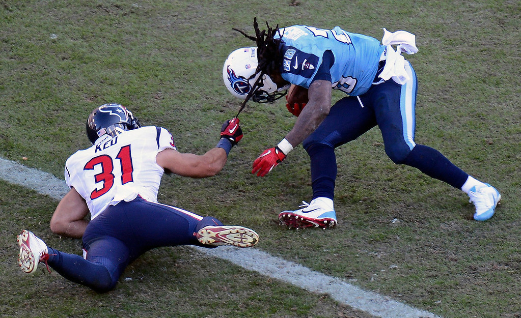 . Tennessee Titans running back Chris Johnson (28) scores a touchdown on an 11-yard run as Houston Texans free safety Shiloh Keo (31) holds on to his hair in the third quarter of an NFL football game on Sunday, Dec. 29, 2013, in Nashville, Tenn. (AP Photo/Mark Zaleski)