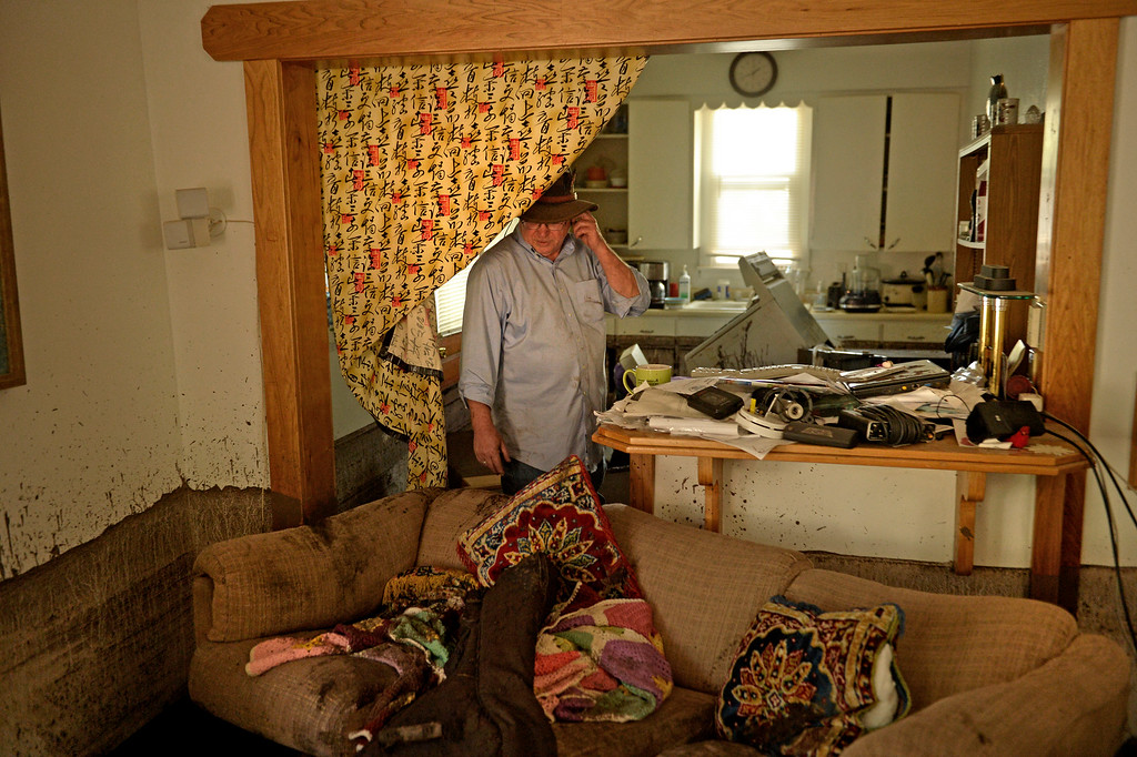 . Manitou Springs, CO. - July 02: Steve Brunette looks over the scrambled living room of his home that is filled with mud after a flash flood washed through houses, streets and businesses when a downpour hit the Waldo Canyon burn scar in El Paso County July 02, 2013 Manitou Springs, Colorado. (Photo By Joe Amon/The Denver Post)