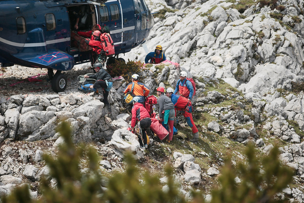 . Rescue workers transport equipment into a police helicopter near the entrance to the Riesending vertical cave after the final phase of the transport of injured spelunker Johann Westhauser to the surface on June 19, 2014 near Marktschellenberg, Germany.(Photo by Johannes Simon/Getty Images)