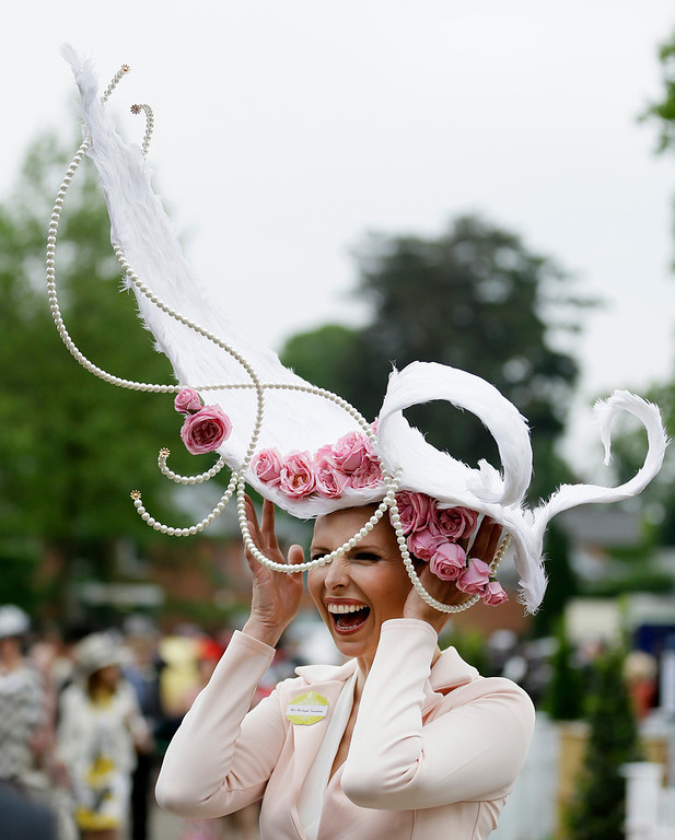 . Anika Svenska laughs a she holds onto her hat as she poses for the media on the first day of the Royal Ascot horse race meeting in Ascot, England, Tuesday, June 18, 2013. (AP Photo/Alastair Grant)