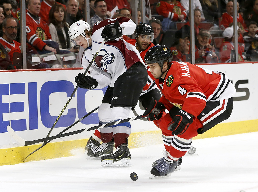 . Colorado Avalanche center Nathan MacKinnon, left, loses the puck as Chicago Blackhawks defenseman Johnny Oduya, center, and defenseman Niklas Hjalmarsson (4) defend during the first period of an NHL hockey game Tuesday, March 4, 2014, in Chicago. (AP Photo/Charles Rex Arbogast)