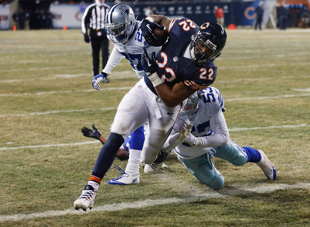 . Chicago Bears running back Matt Forte (22) scores a touchdown past Dallas Cowboys linebacker Cameron Lawrence (53) and safety J.J. Wilcox (27) during the second half of an NFL football game, Monday, Dec. 9, 2013, in Chicago. (AP Photo/Charles Rex Arbogast)