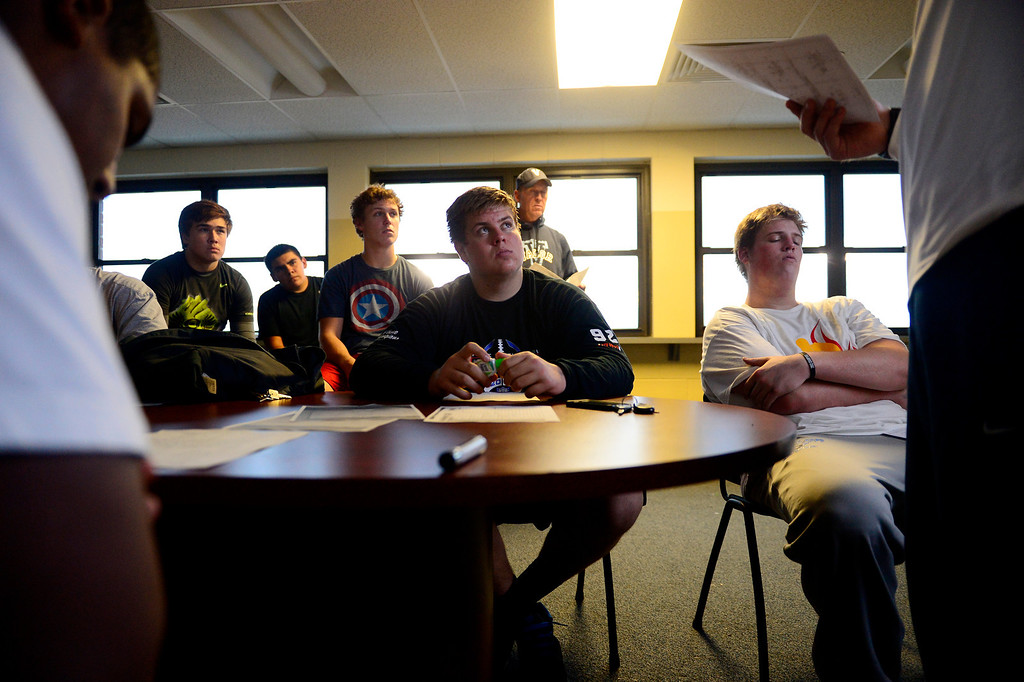 . Valor Christian starting left guard Ryan Cummings (center) and left tackle Alec Ruth (sitting to Cummings\' left) listen during an offensive line meeting.  (Photo by AAron Ontiveroz/The Denver Post)