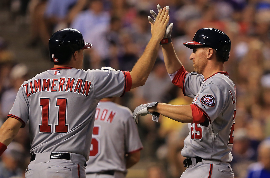 . Ryan Zimmerman #11 and Adam LaRoche #25 of the Washington Nationals celebrate after scoring on a single by Ian Desmond #20 of the Washington Nationals off of Adam Ottavino #0 of the Colorado Rockies to take a 4-0 lead in the sixth inning at Coors Field on June 12, 2013 in Denver, Colorado.  (Photo by Doug Pensinger/Getty Images)