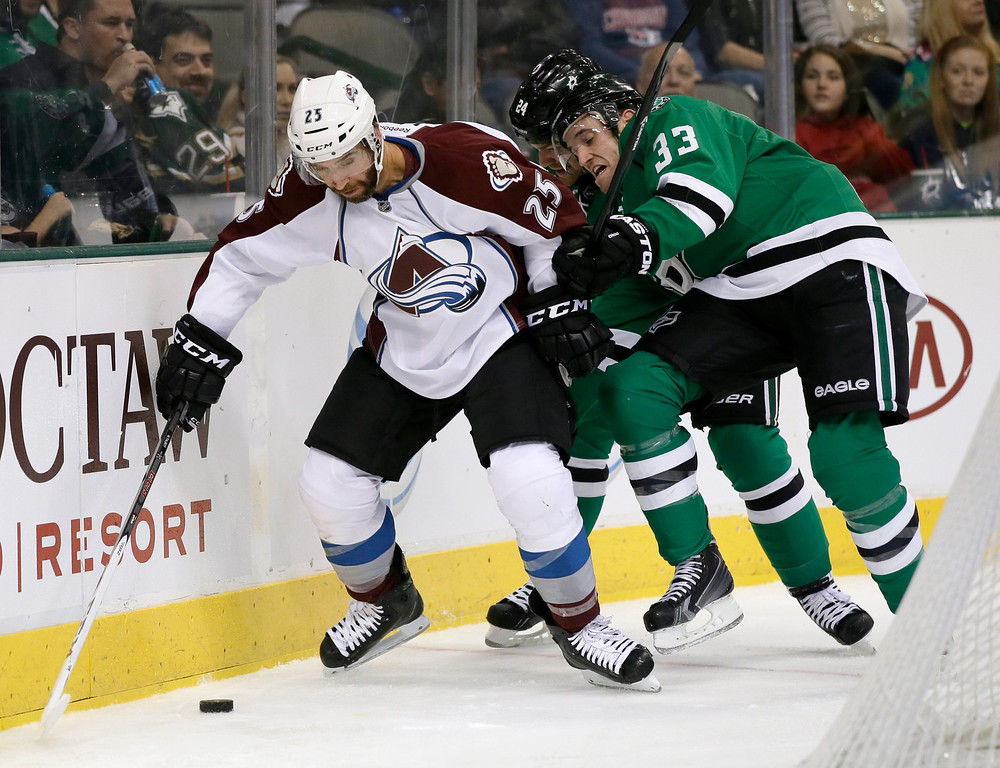 . Colorado Avalanche\'s Maxime Talbot (25) struggles to gain control of the puck against Dallas Stars\' Alex Goligoski (33) and Jordie Benn (24) in the second period of an NHL hockey game, Friday, Nov. 1, 2013, in Dallas. (AP Photo/Tony Gutierrez)