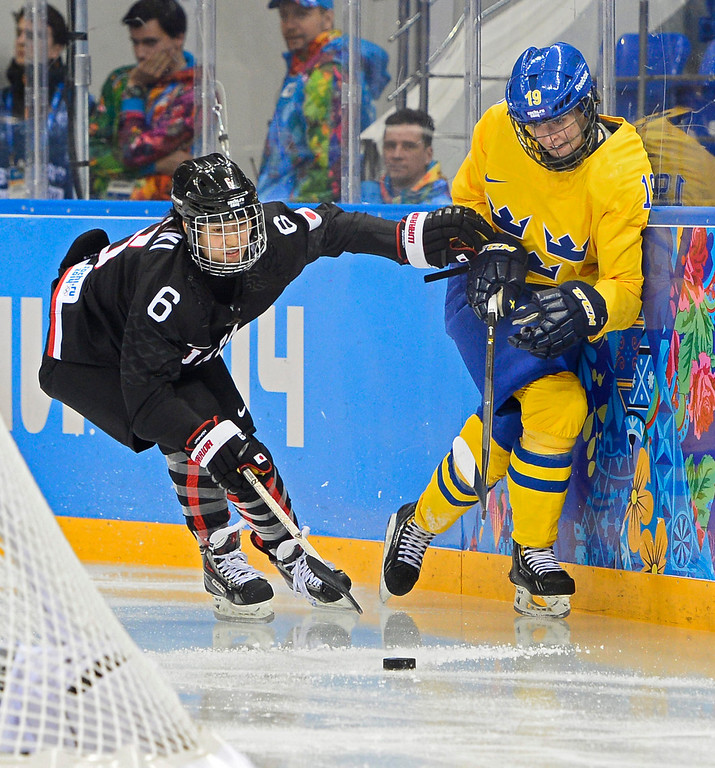 . Linnea Backman (R) of Sweden fights for the puck with Sena Suzuki (L) of Japan in the first period during the match between Sweden and Japan at the Shayba Arena in the Ice Hockey tournament at the Sochi 2014 Olympic Games, Sochi, Russia, 09 February 2014  EPA/LARRY W. SMITH
