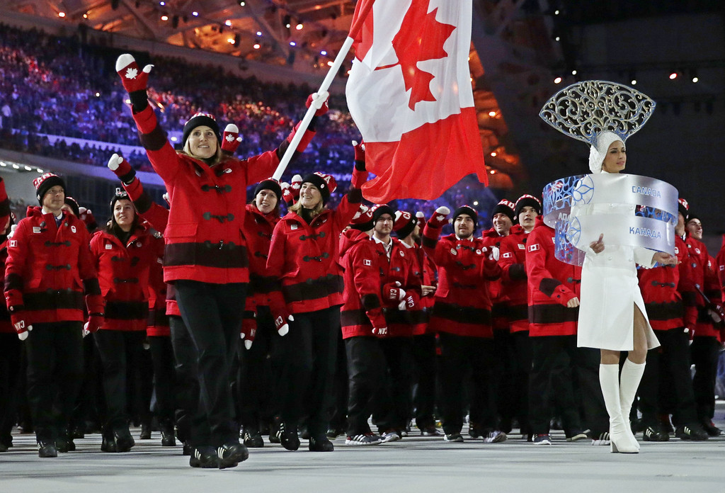 . Hayley Wickenheiser of Canada carries her country flag as they arrive during the opening ceremony of the 2014 Winter Olympics in Sochi, Russia, Friday, Feb. 7, 2014. (AP Photo/Matt Dunham)