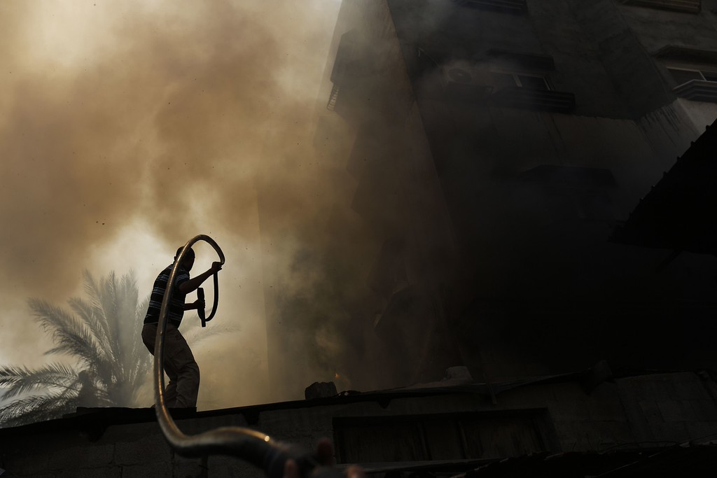 . A Palestinian man battles a building on fire following several Israeli strikes on Gaza City on July 30, 2014. So far, according to Palestinian medics, 1,283 people have been killed and more than 7,170 wounded since the start of the Israeli offensive, which began with an intensive air campaign on July 8 and expanded when Israel sent ground troops into the Gaza periphery on July 17. AFP PHOTO / MOHAMMED  ABED/AFP/Getty Images