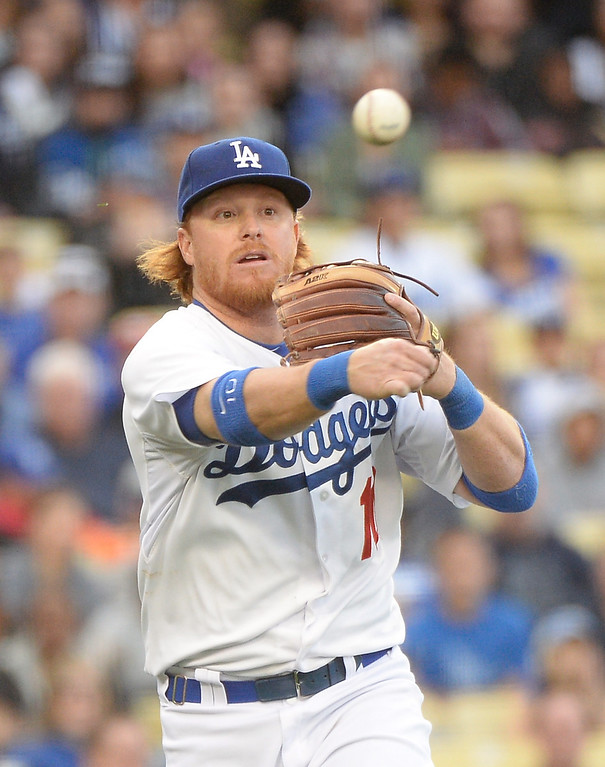 . LOS ANGELES, CA - APRIL 26:  Justin Turner #10 of the Los Angeles Dodgers makes a throw to first for the out of Juan Nicasio #12 of the Colorado Rockies during the third inning at Dodger Stadium on April 26, 2014 in Los Angeles, California.  (Photo by Harry How/Getty Images)