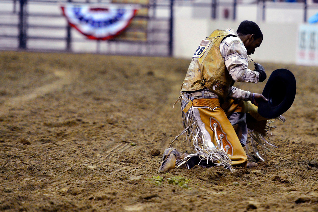 . DENVER, CO. - JANUARY 21:  Nelson Brewster kneels in prayer following his bull ride at the National Western Stock Show Martin Luther King Heritage Rodeo January 21, 2013 (Photo By AAron Ontiveroz / The Denver Post)