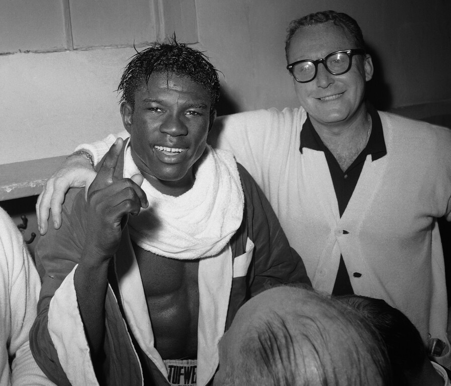 . In this June 8, 1963 file photo, Emile Griffith smiles in the dressing room after regaining his welterweight world championship title by defeating Luis Rodriguez, at New Yorkís Madison Square Garden. At right is Griffith\'s coach, Gil Clancy. Griffith and fellow boxer Ken Norton were among the notables in sports who died in 2013. (AP Photo/File)