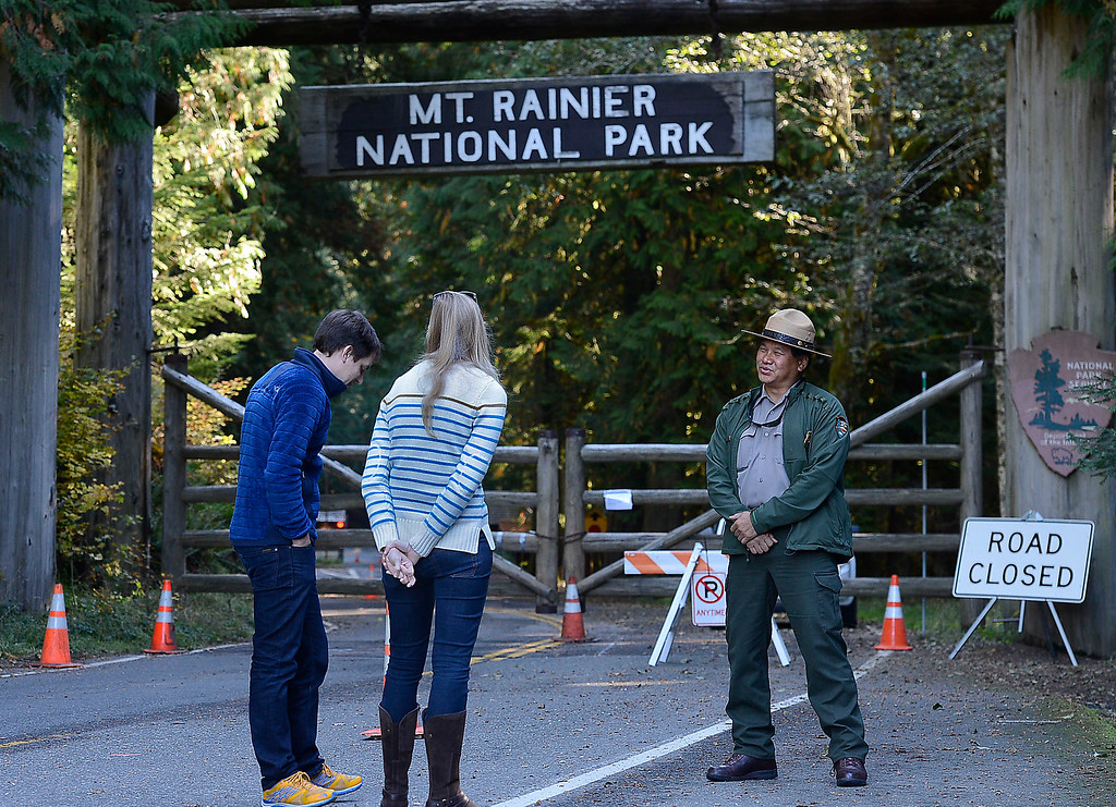 . Chief Ranger Chuck Young, one of 20 park staff considered essential and still working, tells Sean Cameron left, of Seattle and Paige Davis from Mill Valley Calif. that the park was closed, Tuesday, Oct. 15, 2013 at Mount Rainier National Park in Washington.   Gov. Jay Inslee\'s office said the state does not have the money to reopen its popular parks, including Mount Rainier National Park and Mount St. Helens National Volcanic Monument.  (AP Photo/The News Tribune, Dean J. Koepfler)
