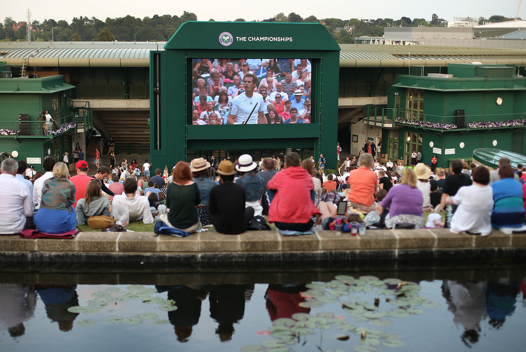 . LONDON, ENGLAND - JULY 05:  Spectators watch a giant TV screen showing Andy Murray of Great Britain\'s men\'s singles semi final match against Jerzy Janowicz of Poland on day eleven of the Wimbledon Lawn Tennis Championships at the All England Lawn Tennis and Croquet Club at Murray Mount on July 5, 2013 in London, England.  (Photo by Peter Macdiarmid/Getty Images)