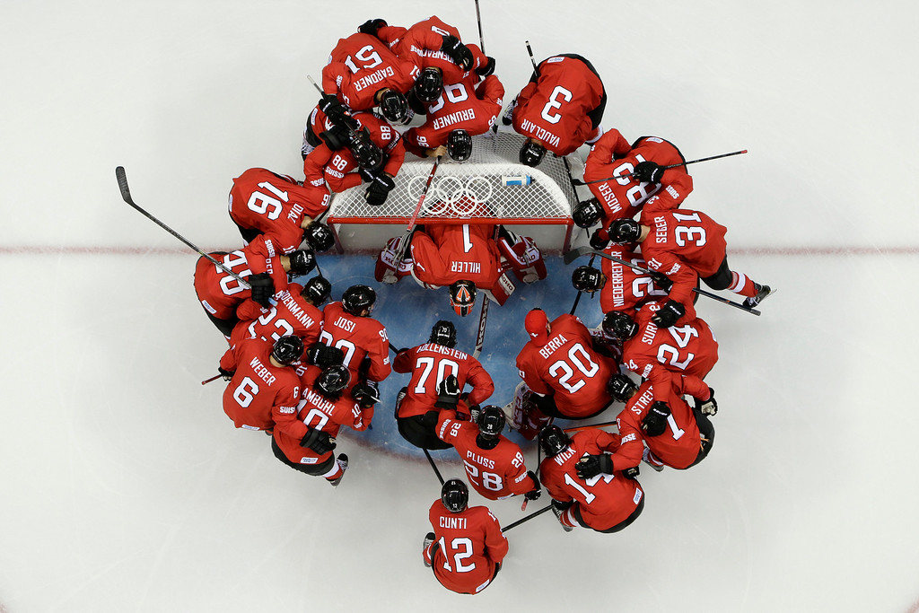. Team Switzerland huddles around the net before their game against Latvia during the 2014 Winter Olympics men\'s ice hockey game at Shayba Arena, Wednesday, Feb. 12, 2014, in Sochi, Russia. (AP Photo/Julio Cortez)