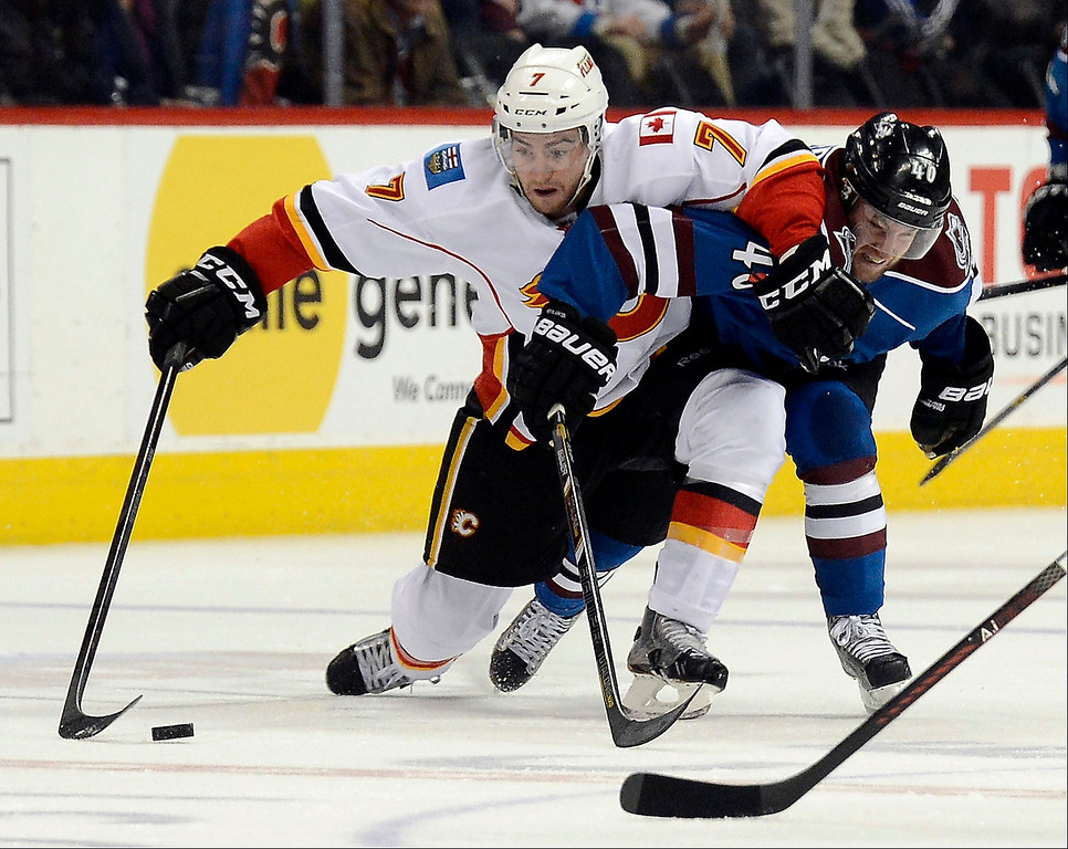 . T.J. Brodie (7) of the Calgary Flames and Mark Olver (40) of the Colorado Avalanche get tangled up as they skate after the puck in the third period April 8, 2013 at Pepsi Center. The Calgary Flames defeated the the Colorado Avalanche 3-1. (Photo By John Leyba/The Denver Post)