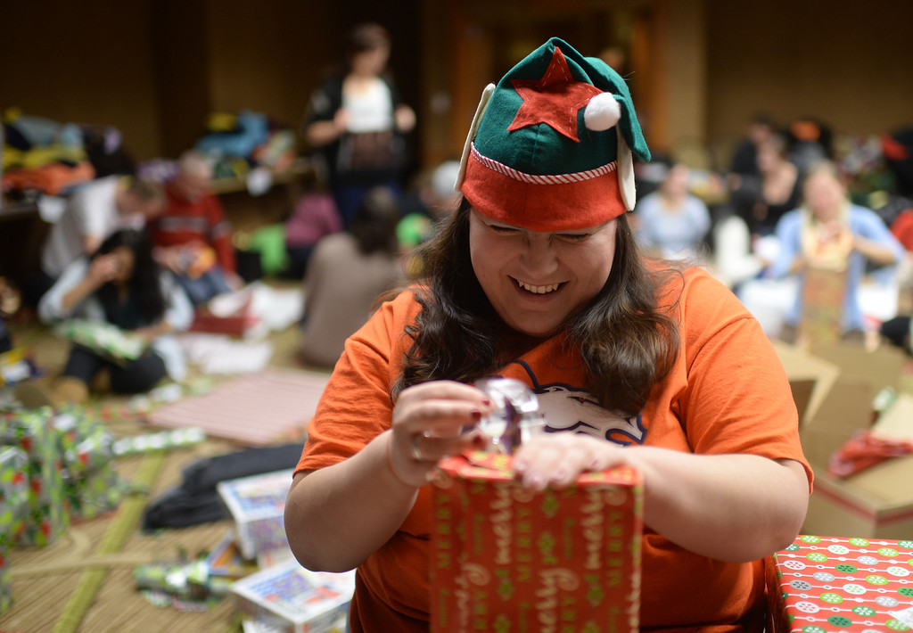 """. DENVER, CO. DECEMBER 21: Leanna Tolmich of Denver is wrapping Christmas gift during the annual Father Woody Christmas Party in Denver, Colorado December 21, 2013. In advance of handing out 5,000 gifts, volunteers are doing a \""""wrapping party\"""" at the Sheraton Denver Downtown Hotel. (Photo by Hyoung Chang/The Denver Post)"""
