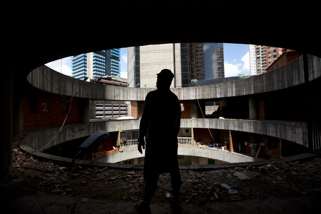. A resident waits for transportation to a new home after being evicted from the worldís tallest slum, the Tower of David, a half-built skyscraper that was abandoned in the 1990s and was transformed by squatters into a vertical ghetto, in Caracas, Venezuela, Tuesday, July 22, 2014. Officials and armed soldiers began moving out the first of thousands of squatters who have lived for nearly a decade in a soaring, half-built skyscraper in the heart of Caracas. (AP Photo/Fernando Llano)