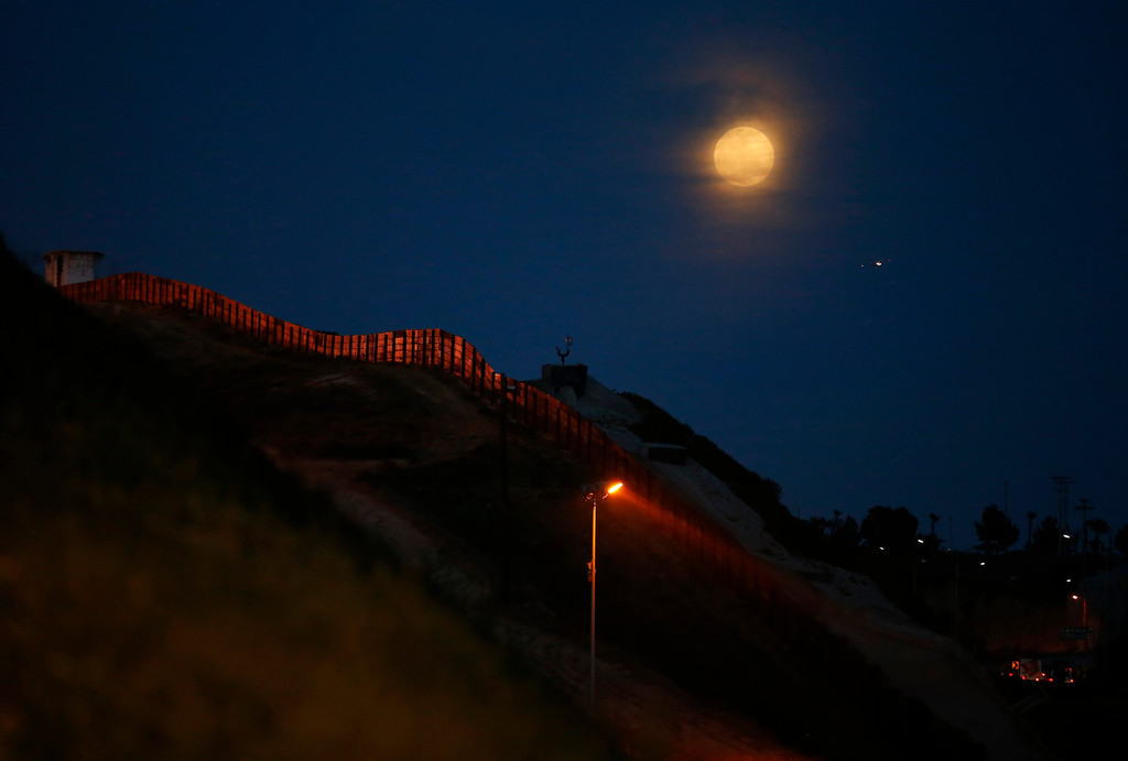 . The moon rises along the primary fence between Mexico and the United States near San Diego, California, March 26, 2013. Picture taken March 26, 2013. REUTERS/Mike Blake