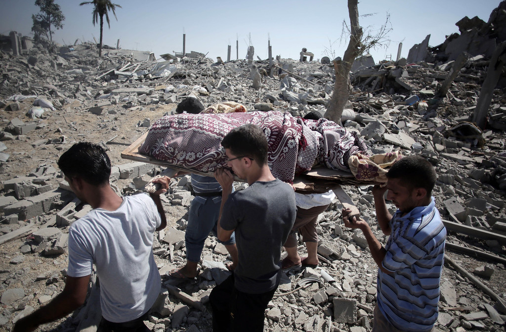 . Palestinians carry a lifeless body found under the rubble while people inspect the damage caused by Israeli strikes in the village of Khuzaa, southern Gaza Strip, close to the Israeli border, Friday, Aug. 1, 2014. A three-day Gaza cease-fire that began Friday quickly unraveled, with Israel and Hamas accusing each other of violating the truce. (AP Photo/Khalil Hamra)