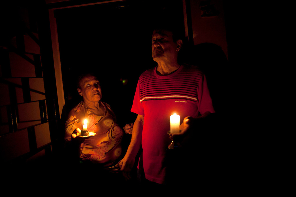""". In this April 8, 2013 photo, Pedro Martinez, 73, right, and his wife Aura, 60, hold lit candles during a power outage at their home in Valencia, Venezuela. \""""This happens nearly every day,\"""" Martinez says of the blackout. It\'s was the day\'s second outage. The first struck just after noon. Outside Venezuela\'s capital, power outages, food shortages and unfinished projects abound; important factors heading into Sunday\'s election to replace Venezuela\'s late President Hugo Chavez, who died last month after a long battle with cancer. Polls show that support for acting President Nicolas Maduro, Chavez\'s hand-picked successor, may be eroding and constant power outages are a testament to the neglect many Venezuelans consider inexcusable in this major oil-producing state. (AP Photo/Ramon Espinosa)"""