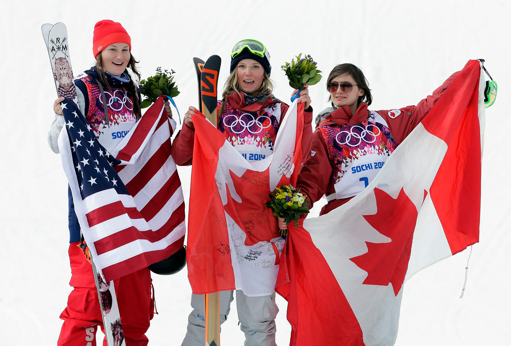 . Canada\'s Dara Howell, center, celebrates on the podium with silver medalist Devin Logan of the United States, left, and Kim Lamarre, right,  also of Canada, after Howell took the gold medal in the women\'s freestyle skiing slopestyle final at the Rosa Khutor Extreme Park at the 2014 Winter Olympics, Tuesday, Feb. 11, 2014, in Krasnaya Polyana, Russia. (AP Photo/Andy Wong)