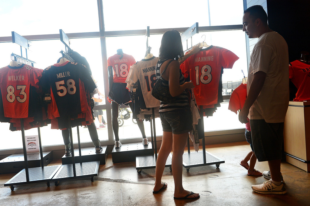 . Terry Martinez shops for Denver Broncos merchandise for her nieces, nephews and her own children with her husband Anthony at the Denver Broncos Team store at of Sports Authority Field at Mile High. Denver is hosting  the NFL season opener with the Denver Broncos taking on the Baltimore Ravens Thursday night.  Photo by Helen H. Richardson/The Denver Post