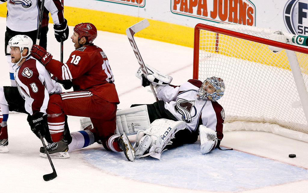 . Phoenix Coyotes\' David Moss (18) and Colorado Avalanche\'s Jan Hejda (8), of the Czech Republic, get up after both collide into Avalanche goalie Semyon Varlamov, of Russia, stays on the ice as a goal is disallowed during the third period of an NHL hockey game Thursday, Nov. 21, 2013, in Glendale, Ariz.  The Avalanche defeated the Coyotes 4-3 in overtime. (AP Photo/Ross D. Franklin)