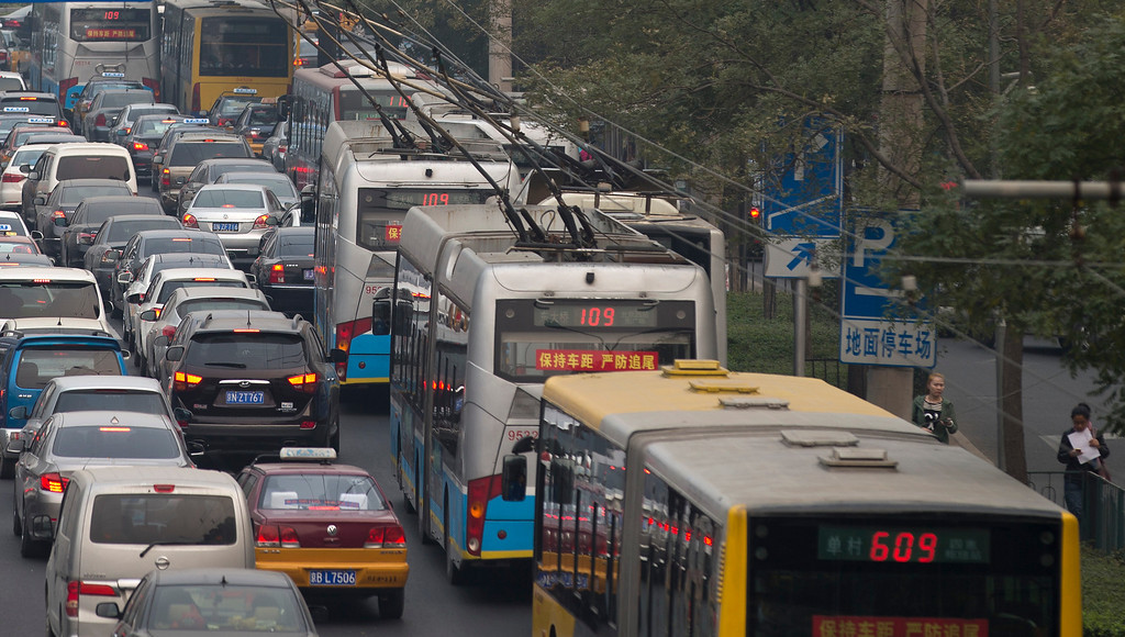 . Chinese women walk past buses and cars clogged with heavy traffic in Beijing Tuesday, Oct. 22, 2013.  (AP Photo/Andy Wong)