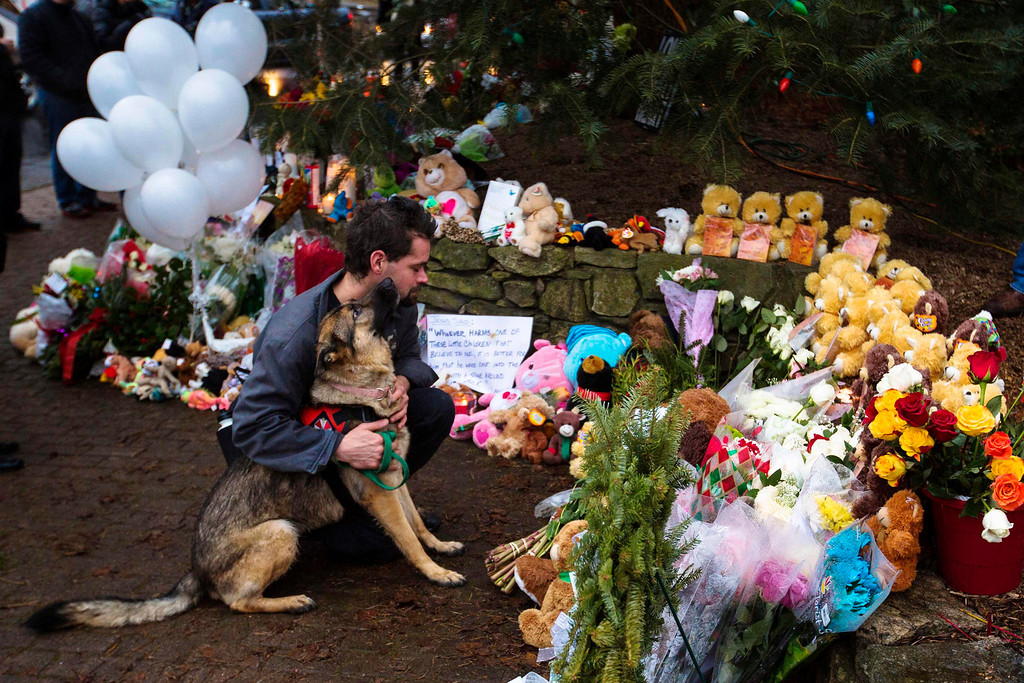 . A man hugs his dog while paying his respects at a memorial to the victims of the recent shooting in Sandy Hook Village in Newtown, Connecticut, December 16, 2012. Twelve girls, eight boys and six adult women were killed in a shooting on Friday at Sandy Hook Elementary School in Newtown.  REUTERS/Lucas Jackson
