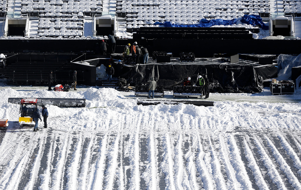 . Workers labor on the field\'s sideline at MetLife Stadium as crews removed snow ahead of Super Bowl XLVIII following a snow storm, Wednesday, Jan. 22, 2014, in East Rutherford, N.J.  (AP Photo/Julio Cortez)