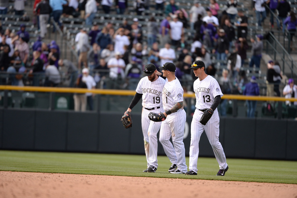 . DENVER, CO. - APRIL 4: Brandon Barnes (1) hugs Charlie Blackmon (19) after the game. At right is Drew Stubbs (13). The Colorado Rockies hosted the Arizona Diamondbacks in the Rockies season home opener at Coors Field in Denver, Colorado Friday, April 4, 2014. (Photo by Hyoung Chang/The Denver Post)