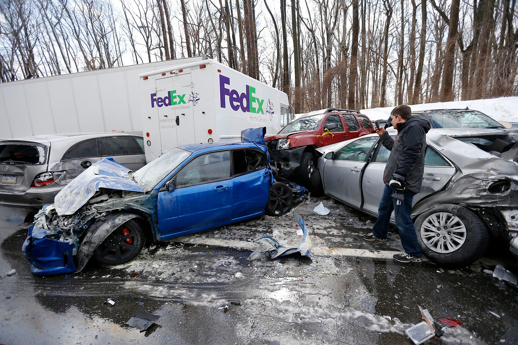 . A man inspects vehicles piled up in an accident, Friday, Feb. 14, 2014, in Bensalem, Pa. Traffic accidents involving multiple tractor trailers and dozens of cars have completely blocked one side of the Pennsylvania Turnpike outside Philadelphia and caused some injuries. (AP Photo/Matt Rourke)