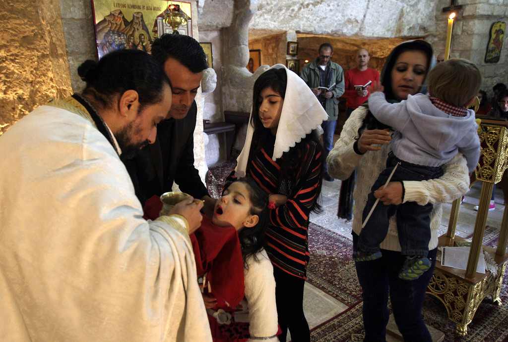 . A Christian priest blesses a Palestinian child during a morning Christmas mass at St. George Melkite Greek Catholic Church, in the West Bank village of Burqin near Jenin city, Wednesday, Dec. 25, 2013. (AP Photo/Mohammed Ballas)
