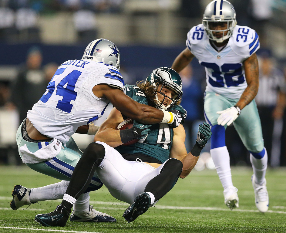 . Bruce Carter #54 of the Dallas Cowboys tackles Riley Cooper #14 of the Philadelphia Eagles in the first half of their game at Cowboys Stadium on December 29, 2013 in Arlington, Texas.  (Photo by Ronald Martinez/Getty Images)